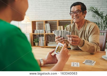 Retired Vietnamese man playing cards with female visitor