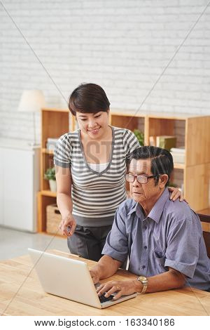 Pretty young woman helping aged man with work on computer