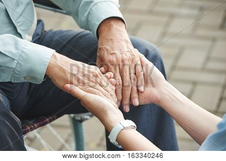 Close-up image of nurse holding hands of mature man