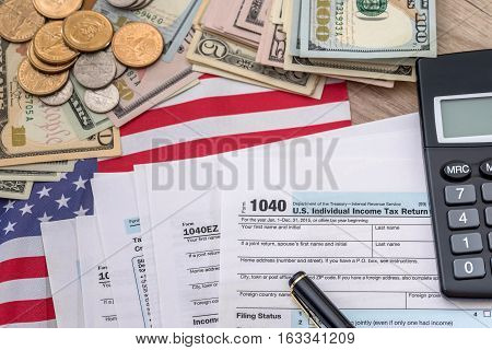 tax concept - 1040 tax form pen us money and flag