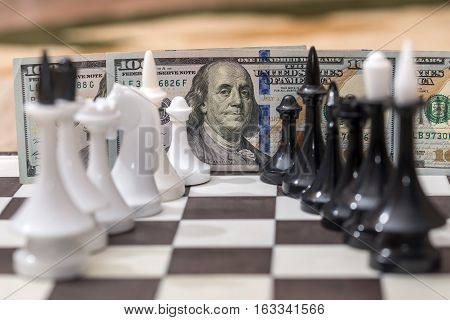 US dollars and chess figures on chessboard