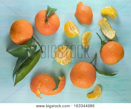 A photo of vibrant orange tangerines with green leaves, slices and peels, shot from above on a teal background texture
