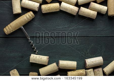 Many wine corks and a vintage cork screw on a dark wooden background texture with copyspace. A horizontal design template for a tasting invitation or restaurant menu