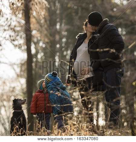 Family life and happiness - pregnant mum and her husband kissing each other standing next to their two kids also giving each other a kiss black dog standing next to them outside in nature.