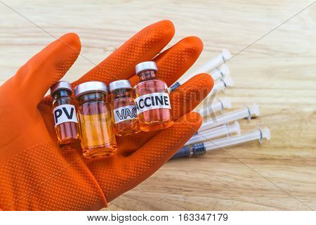 Bottle vaccine of Human papillomavirus (HPV) vaccine in red glove of doctor and disposable syringe on wooden backgroundselective focus