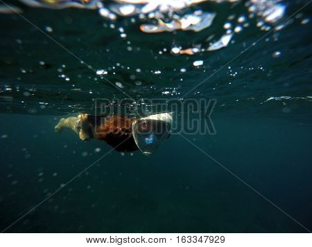 Snorkeling woman underwater in dark sea. Snorkel in full face mask. Female swimmer with loose red hair. Beautiful girl in water. Underwater photo shot in ocean. Tropical vacation activity or sport