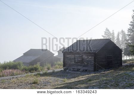Old Wooden warehouse, barns, sheds on the shore. Misty morning by the sea. Trees in the background.