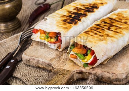 Shawarma with vegetables on a wooden background. Studio Phoho