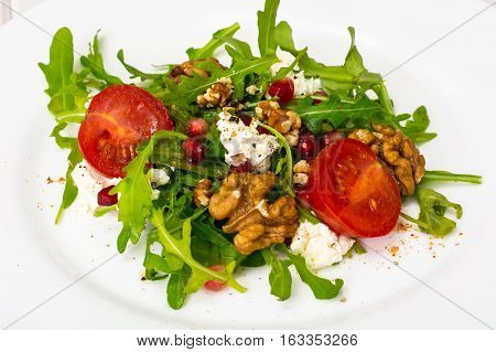 Vegetarian salad with arugula, cherry tomatoes and pomegranate. Studio Photo
