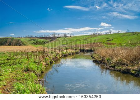 Rural landscape with small river at early spring season.