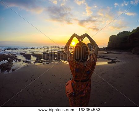 Blur Wide view of Adult Asia Female posting Heart with Arm background Sunset at Bali Indonesia top place to vacation.