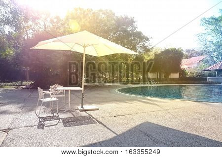 Swimming pool with umbrellas and chairs for relaxing in the hotel. heavy light and bokeh. Tech little artificial light.