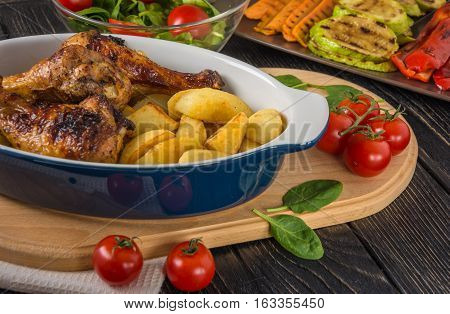 Tasty and nutritious meal with baked chicken drumsticks and potato in ceramic dish grilled vegetables salad and tomatoes on the background of dark table