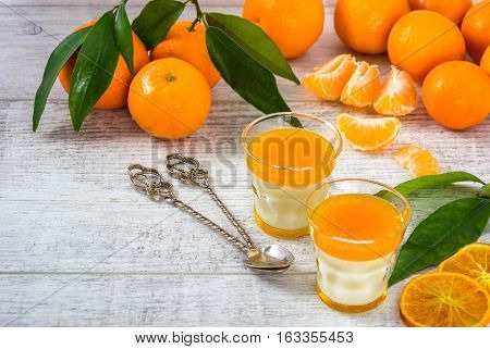 Delicious and rich in vitamins panna cotta with tangerine jam tangerines and slice of tangerines on a white wooden table