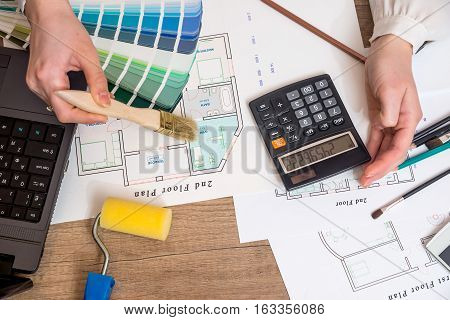 Architect sketching a construction project with laptop color palette and work tools