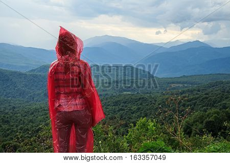 Female traveler in red raincoat stands on the edge of abyss above vast forest territory