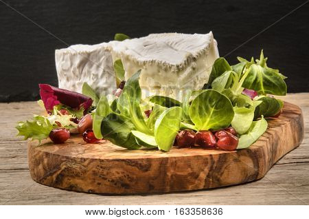 camembert with salad and round cranberry seed on wooden board
