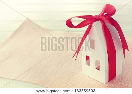 concept with paper model home in a celebratory ribbon with a bow on a clean ground plan / new area for individual real estate construction