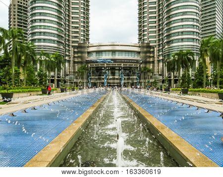 KUALA LUMPUR, MALAYSIA - JANUARY 12, 2014: Petronas Twin Towers and fountain near main entrance. Kuala Lumpur, Malaysia