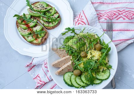 Green salad with avocado couscous and tofu. Open sandwiches with avocado and arugula. Love for a healthy raw food concept.