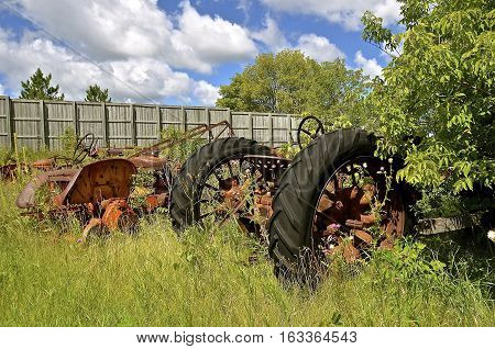 Old tractors are left in the bushes and weeds to be used for salvage and scrap metal.
