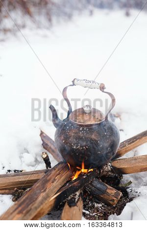 Copper kettle over an open fire in winter. Boiling kettle on firewood. Open fire cooking. Snow around. Lifestyle camping. Blurred background.