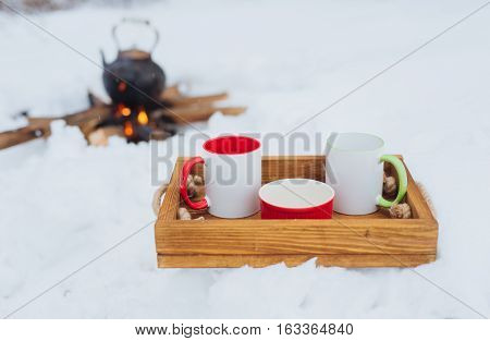 Romantic winter picnic. Two cups and a bowl on a wooden tray in snow. Copper kettle over an open fire on background blurred. Boiling kettle on firewood. Lifestyle camping.