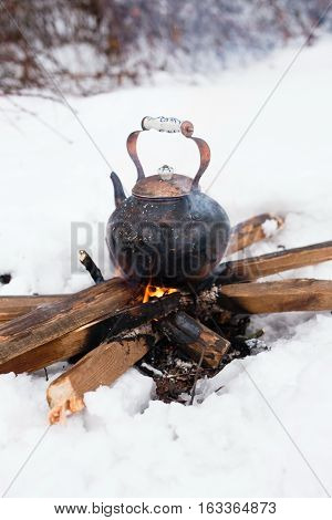 Copper kettle over an open fire in winter. Boiling kettle on firewood. Open fire cooking. Snow around. Lifestyle camping. Blurred background. poster