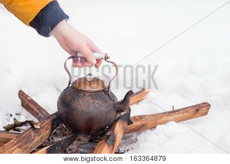 Hand of a man holding copper kettle over an open fire in winter. Boiling kettle on firewood. Open fire cooking. Snow around. Copy space. Lifestyle camping.