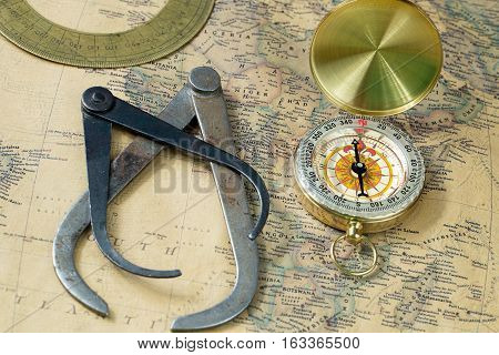 old measuring tool gold compass with cover and protractor on vintage map, macro background, compasses