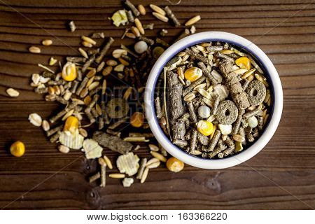 dry food for rodents in bowl on dark wooden background top view.