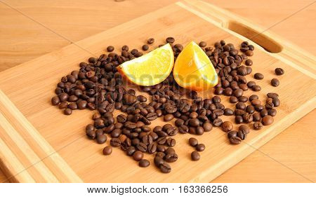 A pile of coffee beans on a board with a couple of orange lobules