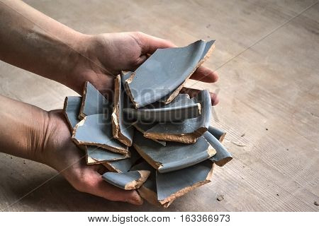 In hand debris or smithereens. Ware splinters in hands closeup. Caucasian man holds in the hands of the debris or fragments of pottery broken plate