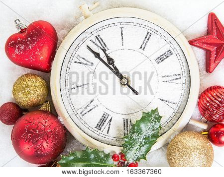 Close up of a clock on new year's eve with christmas decoration on a white background