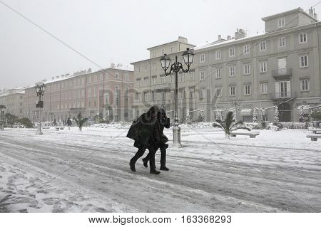 TRIESTE ITALY - DECEMBER 08, 2012: bad weather conditions in Trieste. A man and a woman are walking in the snow and very cold wind known as Bora.