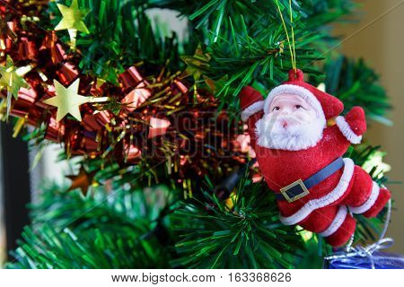 Beautiful decorated Christmas tree with Santaclaus hanging.