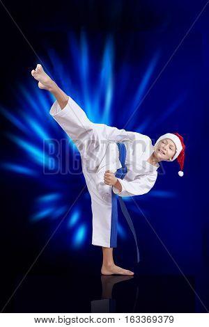 Boy sportsman beats roundhouse kick on the blue background