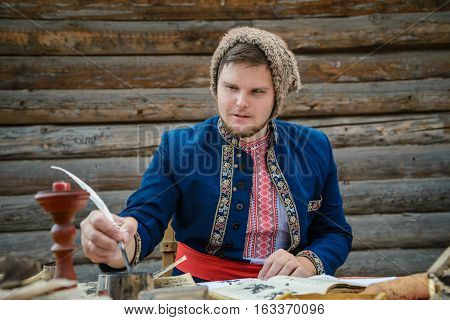 man in traditional ukrainian dress with hat is writing