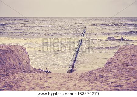Retro Toned Beach With Wooden Breakwater.