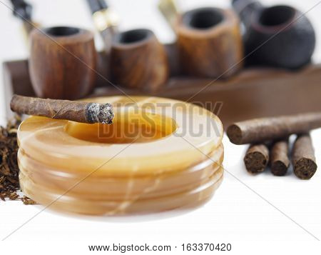 Italian tobacco products. Toscano half cigar burning on an alabaster ashtray.