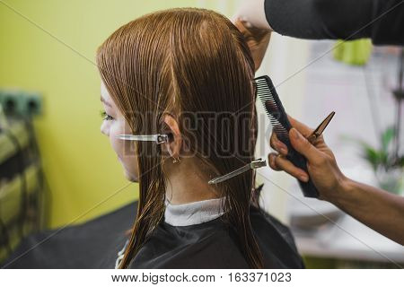 woman is making heir cut in salon with wth hair