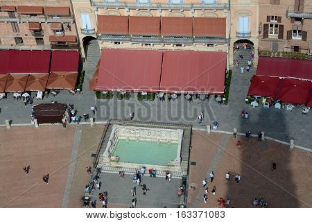 Siena Italy - September 8 2016: Aerial view of fountain on Piazza del Campo in medieval Siena city in Tuscany Italy. Unidentified people visible.