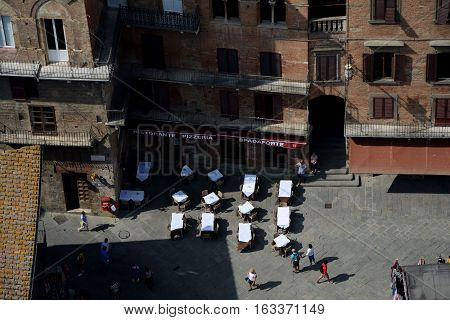Siena Italy - September 8 2016: Tables at restaurant on Piazza del Campo in medieval Siena city in Tuscany Italy. Unidentified people visible.