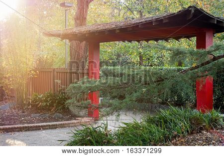 Sydney, Australia - May 22, 2016: At the popular Auburn Botanic Gardens, Japanese Zen Gardens section featuring the Ryoan-ji style designs. A red oriental thatch-roof gate in afternoon atmospheric lighting.