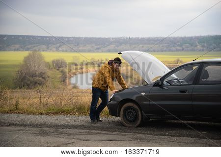 man with broken car in the middle of the road