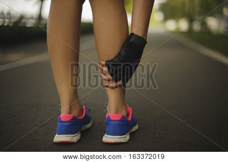 woman massaging legs before the run on the road