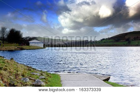 A boat ramp going into the lake with dramatic clouds, also visible a dam and a sail club house