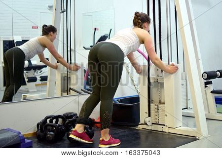 Leg day at the gym. Woman working out her legs with pulley.