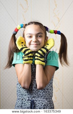 11 year old girl with funny tails of mischievous gum hair dressed in a shirt and dress in mittens the hands are near the face in form of ears.