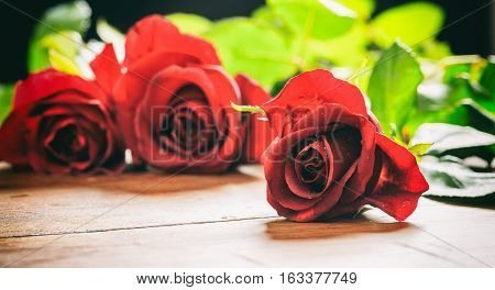 Red Roses On Wooden Table